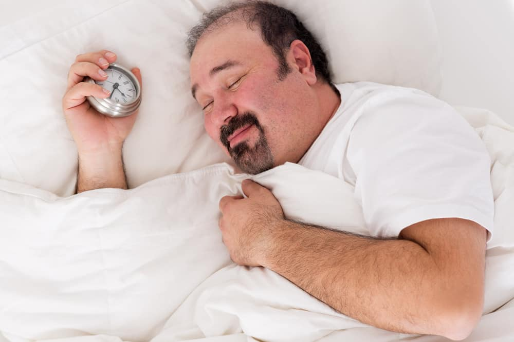 Man smiling in contentment after a good sleep
