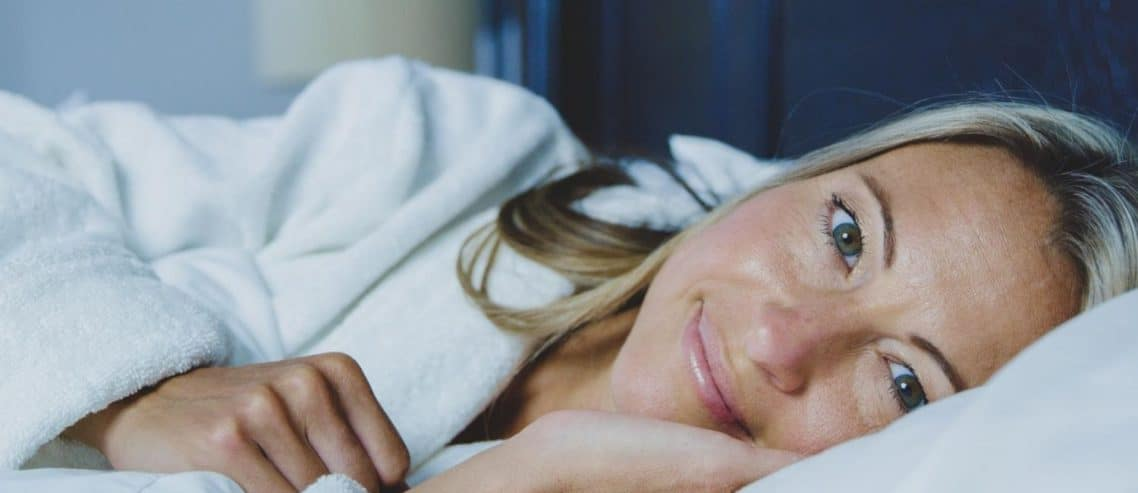 woman-in-white-bed-smiling