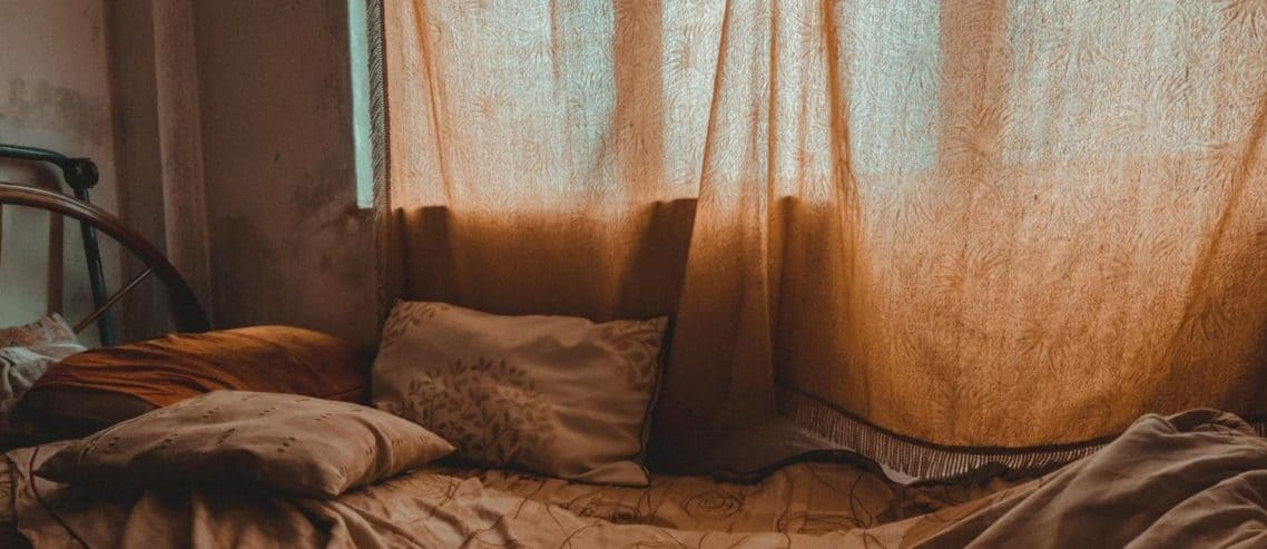 dark-bedroom-with-drapes-and-sheets