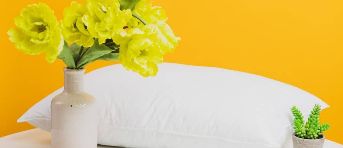 white-pillow-with-yellow-bed-and-flowers